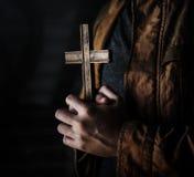 Manos de la mujer adulta que llevan a cabo la cruz que ruega para la religión de dios Fotos de archivo