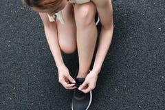 Manos de la mujer asiática sana que ata cordones en las zapatillas deportivas en la calle Concepto de la salud de la aptitud y de fotografía de archivo