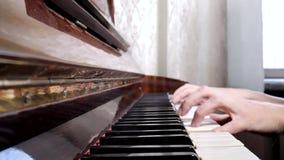 Manos de la mujer caucásica que juegan el piano, cierre para arriba, vista lateral almacen de metraje de vídeo