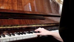 Manos de la mujer caucásica que juegan el piano, cierre para arriba, vista lateral almacen de video