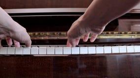 Manos de la mujer cauc?sica que juegan el piano, cierre para arriba, vista lateral metrajes