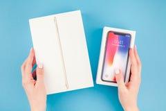 Manos de la mujer con la caja de dispositivos de Apple Imagenes de archivo