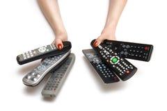 Manos de la mujer con controles de la TV Fotos de archivo