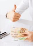 Manos de la mujer con el dinero y los pulgares euro del efectivo para arriba Fotografía de archivo libre de regalías