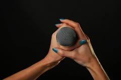 Manos de la mujer con el micrófono aislado en negro Foto de archivo
