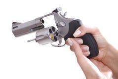Manos de la mujer con el revólver con el shell pasado Fotos de archivo
