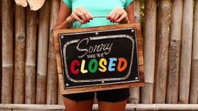 Manos de la mujer con el tablero cerrado de la muestra en un fondo tropical de la naturaleza Isla de Bali almacen de video