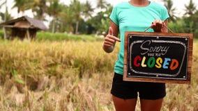 Manos de la mujer con el tablero cerrado de la muestra en un fondo tropical de la naturaleza Isla de Bali almacen de metraje de vídeo