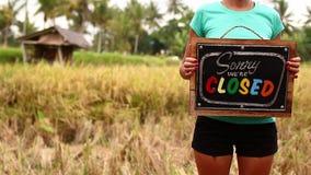 Manos de la mujer con el tablero cerrado de la muestra en un fondo tropical de la naturaleza Isla de Bali metrajes