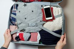 Manos de la mujer con el teléfono en el fondo de la maleta Open lleno foto de archivo libre de regalías