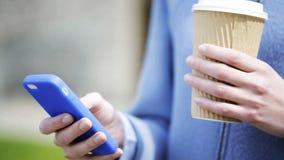 Manos de la mujer con la taza y el smartphone de café almacen de video