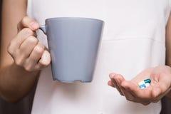 Manos de la mujer con las píldoras y taza de agua Fotos de archivo