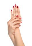 Manos de la mujer con los clavos rojos de la manicura Fotografía de archivo