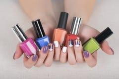 Manos de la mujer con los esmaltes de uñas y la manicura colorida brillante Imagen de archivo