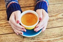 Manos de la mujer con la taza de café caliente fotografía de archivo