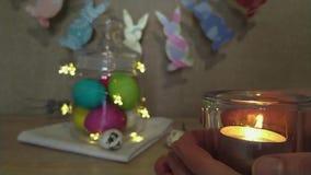 Manos de la mujer de la decoración de Pascua que llevan a cabo la vela