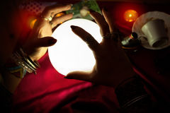 Manos de la mujer del adivino sobre la bola de cristal iluminada Foto de archivo