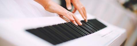 Manos de la mujer del primer que juegan la bandera horizontal del piano foto de archivo