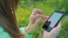 Manos de la mujer del primer usando el teléfono de la pantalla táctil al aire libre metrajes