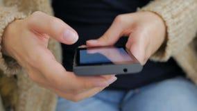 Manos de la mujer del primer usando smartphone almacen de metraje de vídeo
