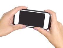 Manos de la mujer dos que sostienen el teléfono móvil y que toman la imagen, aislante Foto de archivo libre de regalías