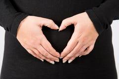 Manos de la mujer embarazada que esperan a un bebé deseado Imagenes de archivo