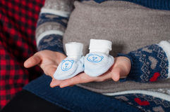 Manos de la mujer embarazada que sostiene los pequeños zapatos Imágenes de archivo libres de regalías