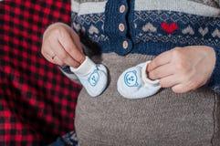 Manos de la mujer embarazada que sostiene los pequeños zapatos Fotos de archivo libres de regalías