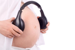 Manos de la mujer embarazada que sostienen los auriculares Fotos de archivo libres de regalías