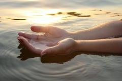 Manos de la mujer en agua Fotos de archivo libres de regalías