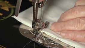 Manos de la mujer en la cámara lenta frecuencia intermedia del primer lateral de la máquina de coser almacen de metraje de vídeo