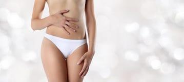 Manos de la mujer en el vientre, en fondo borroso de las luces imágenes de archivo libres de regalías