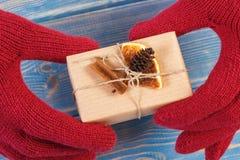 Manos de la mujer en guantes con el regalo adornado para la Navidad o la otra celebración Fotos de archivo libres de regalías