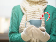 Manos de la mujer en las manoplas de lana blancas que sostienen una taza acogedora con cacao, té o café caliente Concepto del tie Imágenes de archivo libres de regalías