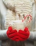 Manos de la mujer en los guantes rojos de lana que sostienen la taza acogedora con cacao, té o café y bastón de caramelo caliente Fotos de archivo
