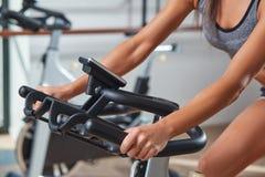 Manos de la mujer en una bici inmóvil de la barra el gimnasio imagenes de archivo