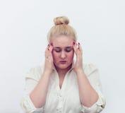 Manos de la mujer joven en el dolor de cabeza principal en blanco Imagen de archivo