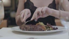 Manos de la mujer joven que cortan el filete sabroso que miente con las verduras y las hojas en la placa en el restaurante vidrio metrajes