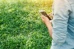 Manos de la mujer joven usando su teléfono móvil en los prados Fotografía de archivo libre de regalías