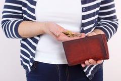 Manos de la mujer mayor con las monedas y de la cartera de cuero, concepto de seguridad financiera en edad avanzada Imagen de archivo libre de regalías