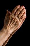 Manos de la mujer mayor en un negro Imagen de archivo