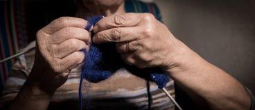 Manos de la mujer mayor que hacen punto con lanas y agujas que hacen punto Imagen de archivo libre de regalías