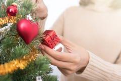 Manos de la mujer que adornan el árbol de navidad Fotografía de archivo