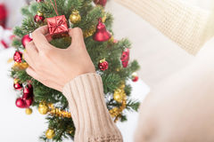 Manos de la mujer que adornan el árbol de navidad Fotos de archivo