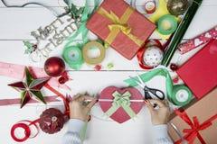 Manos de la mujer que adornan el regalo de la Navidad foto de archivo libre de regalías