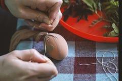 Manos de la mujer que adornan y que pintan los huevos de Pascua Imagen de archivo libre de regalías