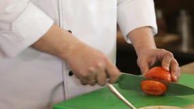 Manos de la mujer que cortan el tomate en cocina almacen de video