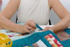 Manos de la mujer que cosen para el final un edredón fotografía de archivo libre de regalías