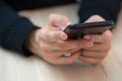 Manos de la mujer que envían el mensaje usando el teléfono elegante foto de archivo