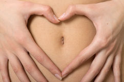 Manos de la mujer que forman símbolo del corazón alrededor de ombligo Imagenes de archivo